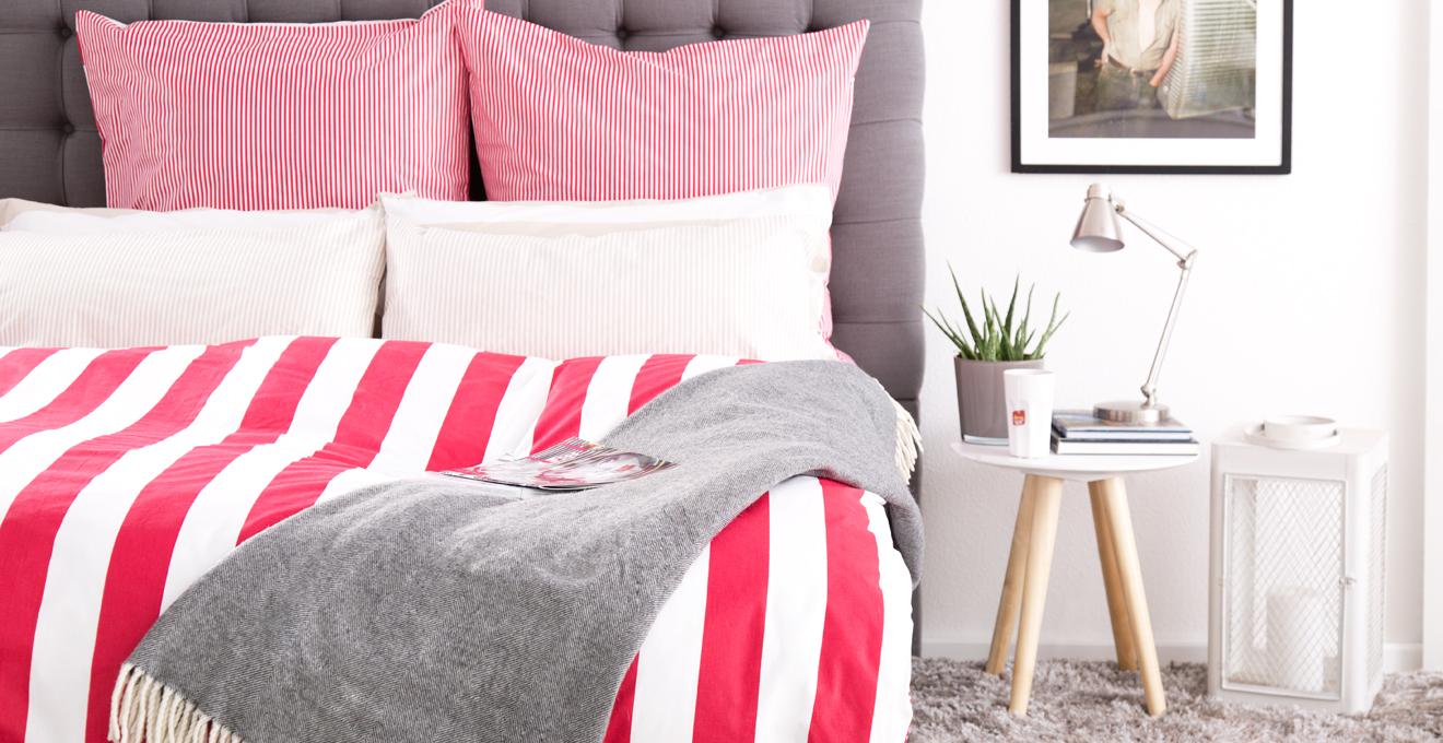 šedá postel boxspring s pruhovaným povlečením