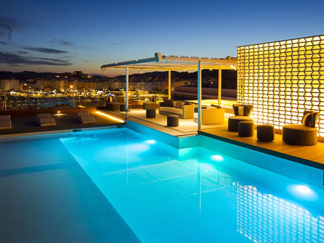 Los juegos de luces y la infinita calma y elegancia que desprenden las terrazas con estilo del Hotel Aguas de Ibiza son una irrechazable invitación a disfrutar al aire libre de sus piscinas o de un buen cóctel mientras se contempla la esencia de la isla blanca.
