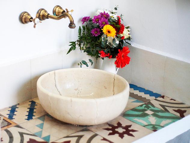 Después de atravesar unas puertas de carpintería en azul claro accedemos a los baños, revestidos con azulejos antiguos con distintos dibujos que recuerdan a las baldosas hidráulicas.