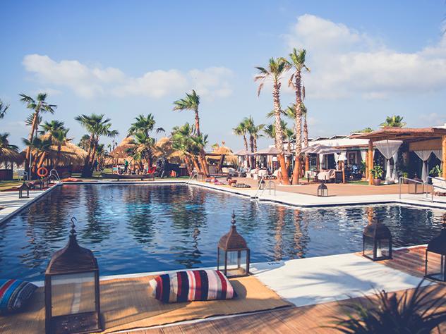 Faroles de inspiración oriental, alfombras lisas que evocan a la naturaleza, cojines a rayas y palmeras de fondo alrededor de la piscina son el pretexto para la impresionante terraza del restaurante Trocadero Sotogrande, en Cádiz.