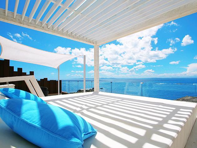 El intenso azul del cielo y las caprichosas nubes blancas son el techo de la terraza del Hotel Vistabella, cuyos colores inspiran la decoración de las camas chill out con dosel.