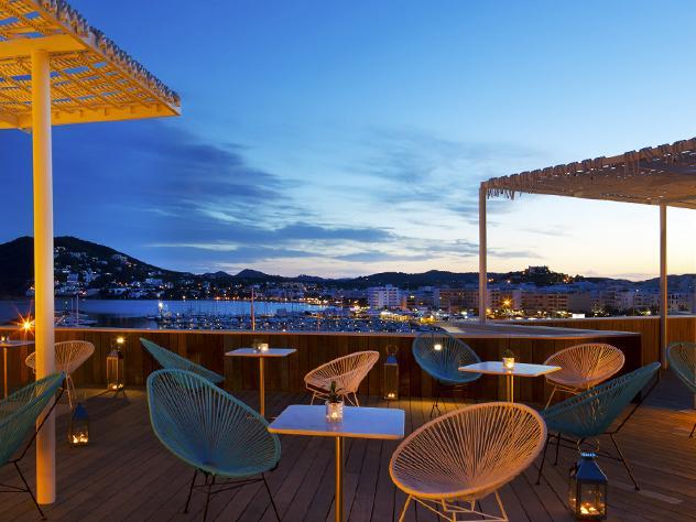 El diseño de las piezas que conforman las terrazas del Hotel Aguas de Ibiza, situado en el Paseo Marítimo de Santa Eulalia,  y la tenue iluminación del lugar invitan a disfrutar de las maravillosas vistas de la zona.