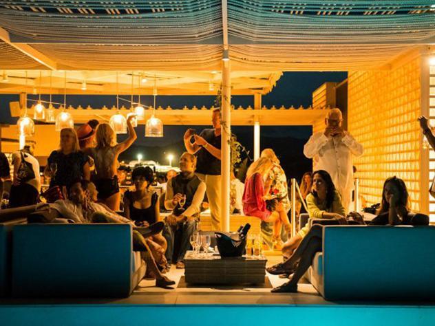 Los toldos de la terraza se visten de blanco, el color de la isla, y de ellos desprenden las diáfanas lámparas de techo, creando así un ambiente íntimo para disfrutar en pareja o entre amigos.