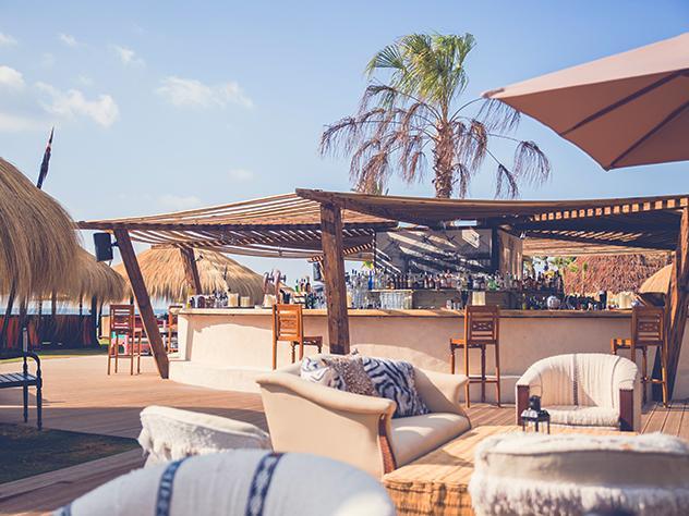 El eclecticismo de la terraza se confirma con la presencia de la barra de bebidas. Cubierta por una estructura de madera, su forma y los cuadros que visten sus paredes dejan entrever los guiños asiáticos que se saborearán en los platos de esencia mediterránea.