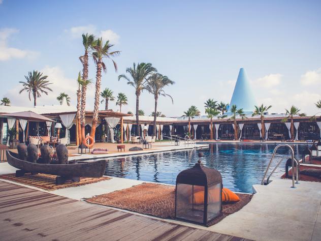 La figura escultórica de una canoa africana acompañada por alfombras, cojines y faroles preside la piscina, el centro neurálgico de este restaurante.