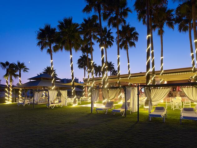 Cuando cae la noche la iluminación entra en juego formando curiosas formas, como con las guirnaldas de luces que escalan los troncos de las palmeras, creando así un ambiente mágico.