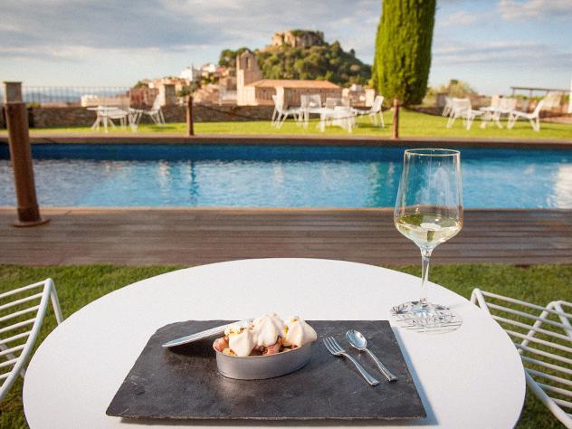 Sentarse frente a la piscina y las imponentes vistas de La Masía de Can Marc a disfrutar de su variado surtido de tapas para picar o cenar de forma informal es todo un lujo para la vista y el paladar.
