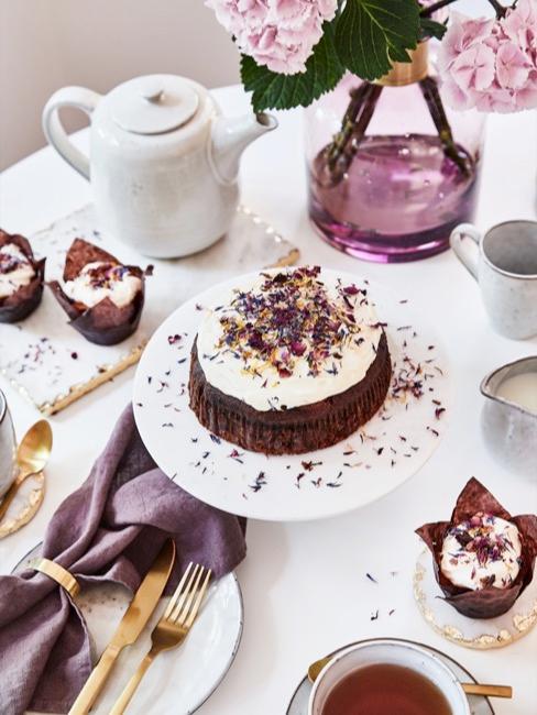 mesa blanca con set de café, pasteles y decoración de color lila