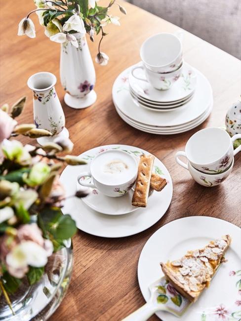 Nahaufnahme gedeckter Ostertisch mit blumigem Geschirr, Kuchen und Blumen