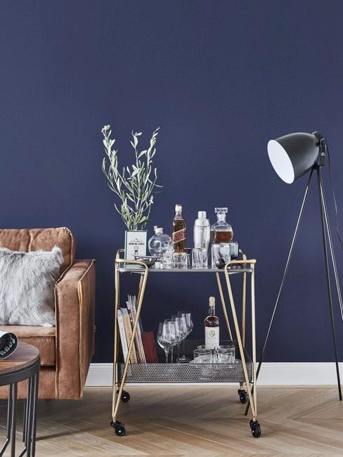 Soggiorno con divano marrone e parete blu