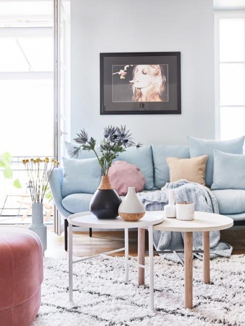 Salotto tonalità chiare con divano azzurro pastello e tavolini minimal
