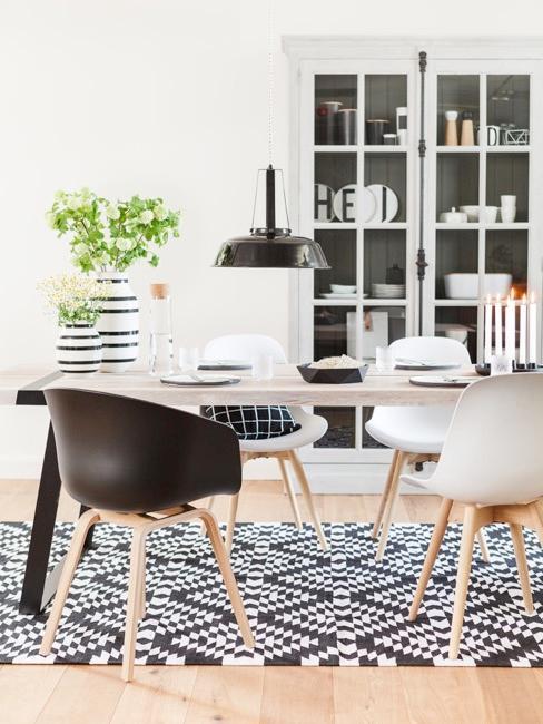 Sala da pranzo in stile hygge con tappetto geometrico e sedie minimal