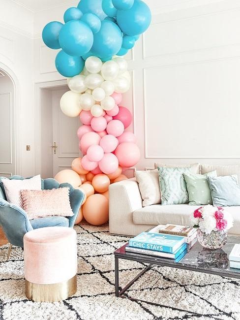 Globos de colores en un salón decorado en tonos verde, rosa y blanco