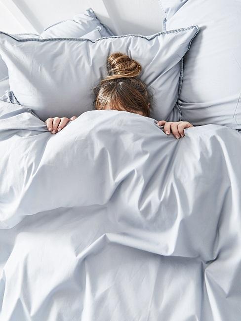 Frau im Bett bei einer Pyjama-Party
