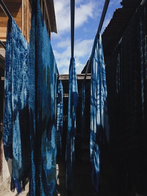 Shibori Textilien aufgehängt auf Wäscheleinen zwischen Häusern