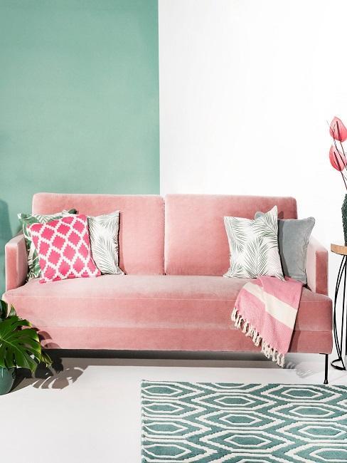 Sofá rosa con cojines y fondo de pared en dos colores, verde y blanco