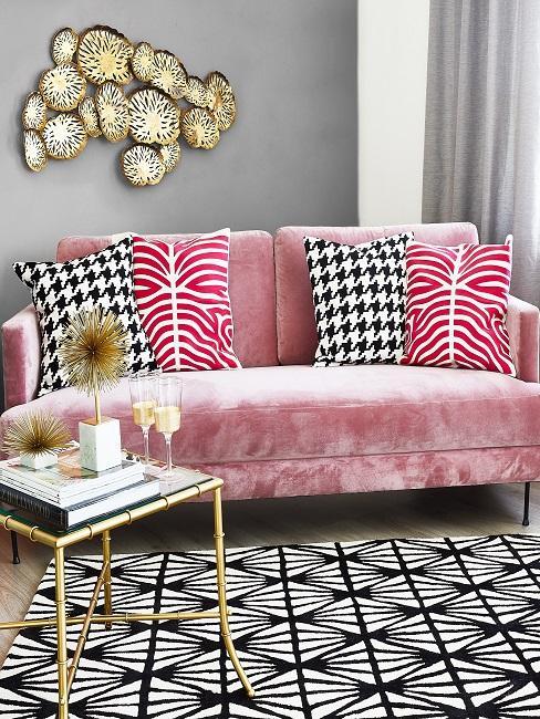 Sofá rosa con cojines de colores, alfombra en blanco y negro y pared de fondo gris