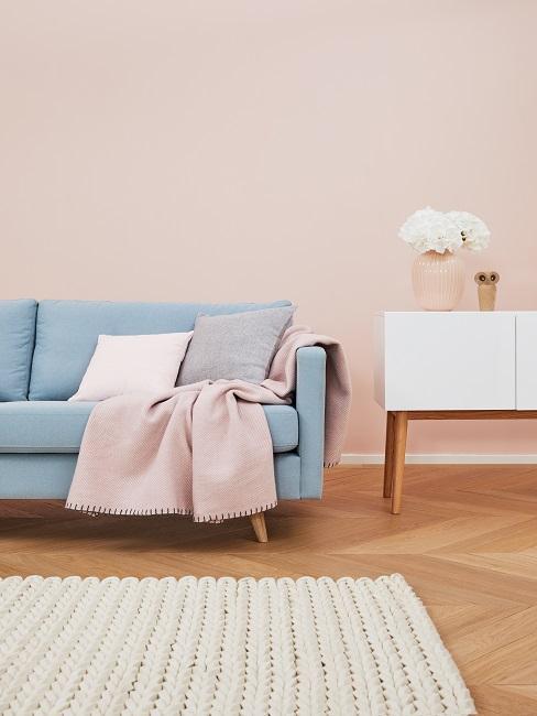 sofá de color azul pastel, con manta rosada, alfombra clara