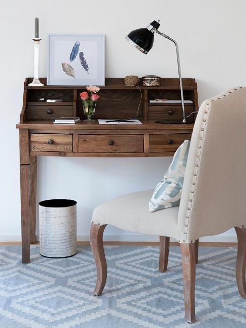 Ein alter Holz-Schreibtisch mit Deko hinter einem hellen Stuhl im Landhausstil