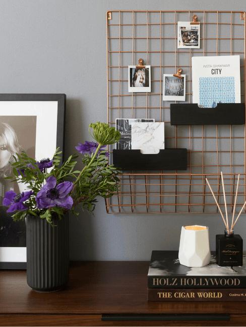 Dettaglio accessori su scrivania, con fiori e griglia appesa al muro