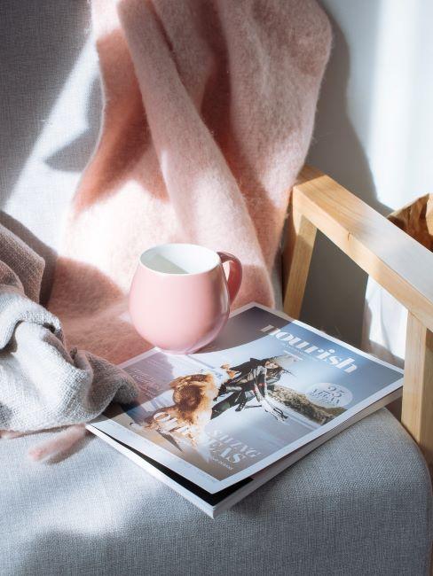 poltrona con rivista di viaggi, tazza rosa e coperta