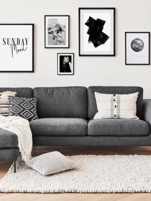 Salon w stylu skandynawskim utrzymany w biało-szarej kolorystyce. Na środku szra sofa z ozdobnymi poduszkami, biały dywan, a na ścianie czarno-białe fotografie.