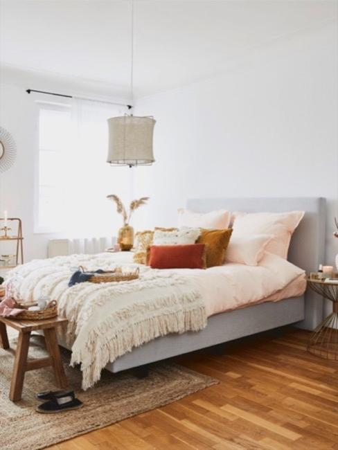 Schlafzimmer mit großem Bett, Tagesdecke im Ethno Stil und Möbelstücke und Deko aus Naturmaterialien