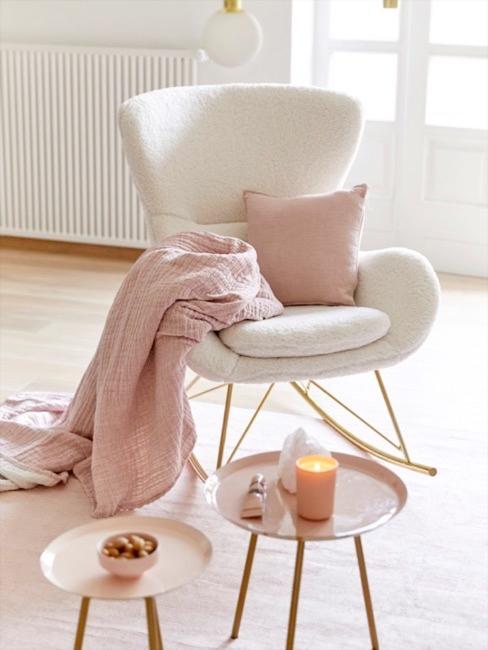 Sofá de borreguito blanco con base dorada, combinada con mantas, cojines y mesitas de color rosa