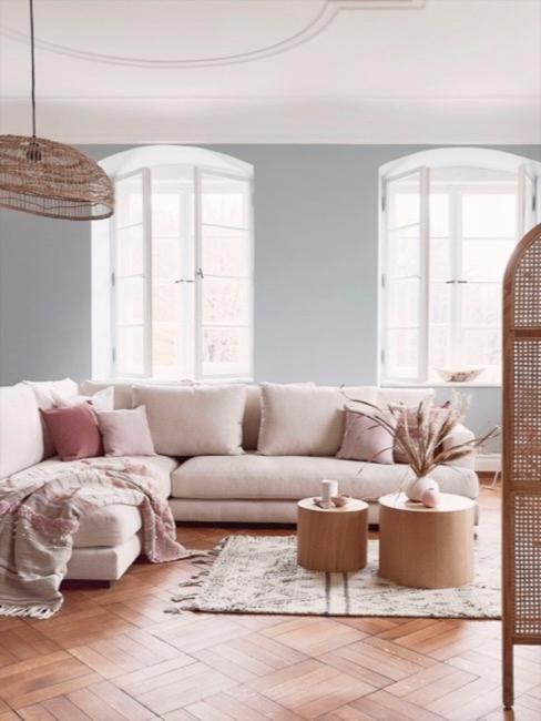 Raumtrenner aus Wienergeflecht im Vordergrund. Im Hintergrund helle Wohnzimmerlandschaft mit beigem Big-Sofa.