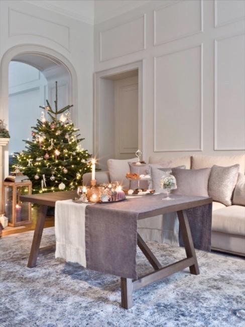 Festlich gedeckter Tisch vor dem Sofa, dahinter ein Weihnachtsbaum