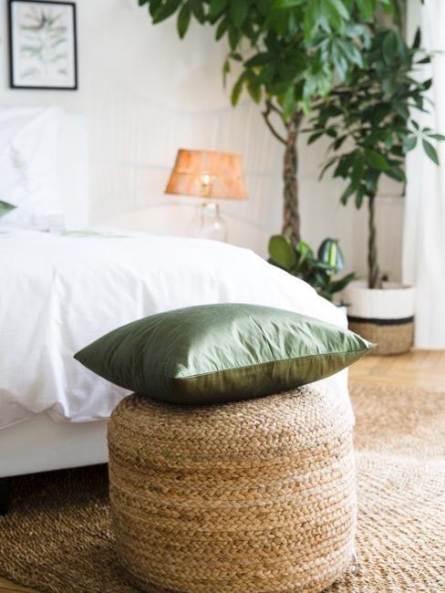 Cojín verde sobre puf de mimbre con una cama blanca, una lámpara naranja y dos plantas de fondo