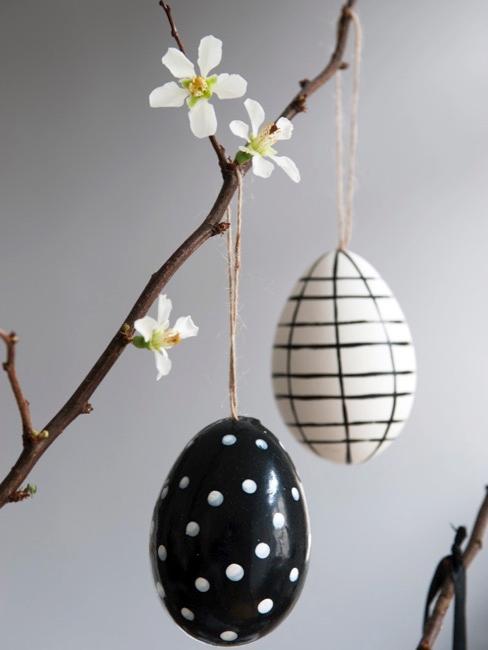 Uova di pasqua dipinte in bianco e nero appese a un ramo