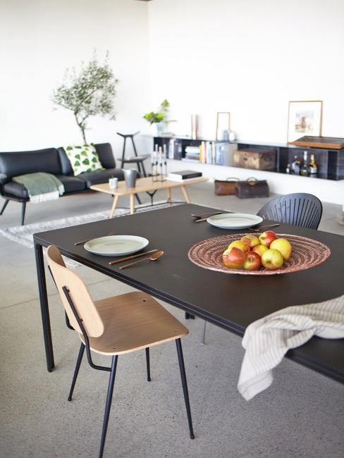 Salon połączony z jadalnią z czarnym stołem i drewnianymi krzesłami