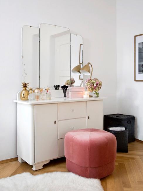 Credenza in camera da letto riempita di vestiti e utilizzata come tavolino da toilette
