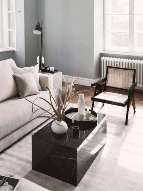 Salon de style moderne avec une table basse en marbre noir un canapé gris et un fauteuil noir en rotin