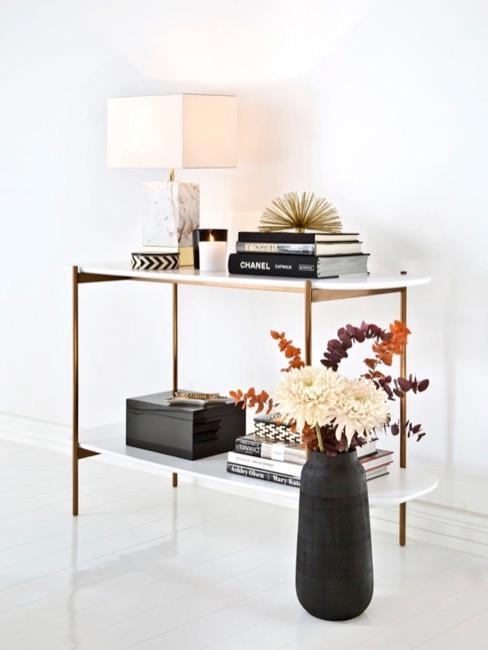 Table blanc crème avec plusieurs accessoires de décoration en noir et blanc comme des livres, une lampe ou un vase