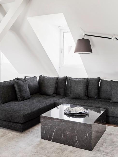 Jasne pomieszczenie z ukośnymi ścianami oraz jednym oknem, z czarną narożną kanapą po środku przed którą stoi nowoczesny stoil kawowy oraz wiszącą lampą nad kanapą