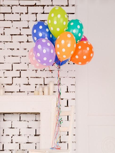 Bunte Luftballons mit Punkten vor einer Wand an einem Stuhl angebunden