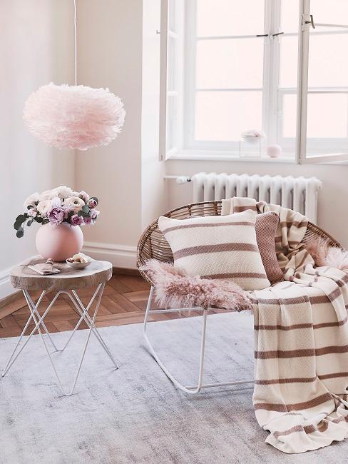 Lámpara de plumas, mesa axiliar con jarrón rosa y sillón decorado con manta y cojín a rayas