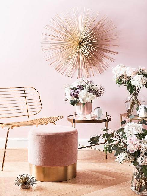 Wohnzimmer Arrangement mit Stuhl, Couchtisch und Pouf, daneben sehr viele Blumegestecke in Vasen vor einer rosafarbenen Wand