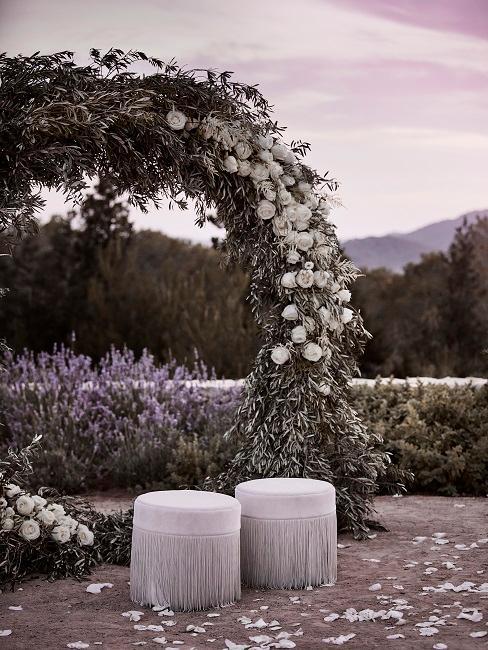 Matrimonio in giardino: due pouf bianchi con frange davanti a un arco fiorito con rose bianche