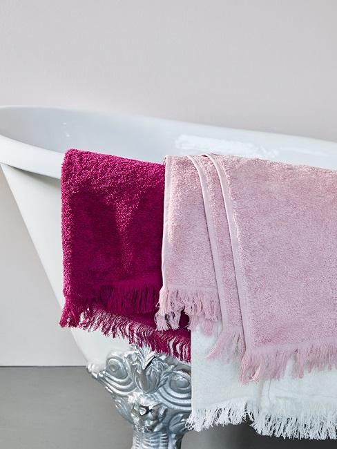 Vasca da bagno con molti asciugamani appesi al bordo