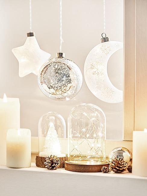 Fensterbrett mit Kerzen, hängenden Weihnachtskugeln und leuchtender Deko im Glas