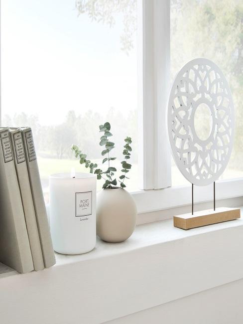 Fensterbank mit weißer Deko und Duftkerze