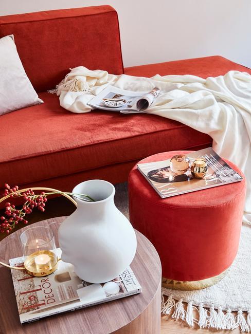 Rincón de lectura con sofá y puf en tonos rojos y dorados