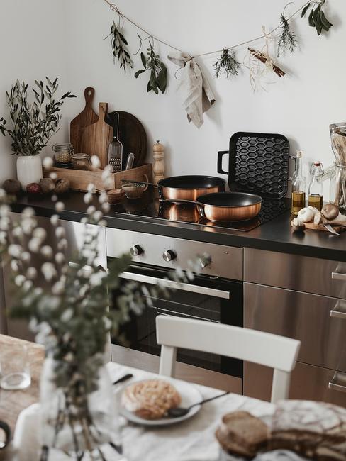 Jasna kuchnia z drewnianym stołęm, białym krzesłem, aneksem kuchennym i suszonymi roślinami na ścianie