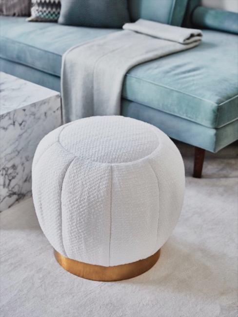 Puf blanco de material bouclé con fondo de sofá azul claro y manta gris