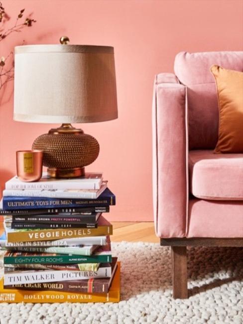 Salón en color coral con sofá, libros y lámpara de mesa