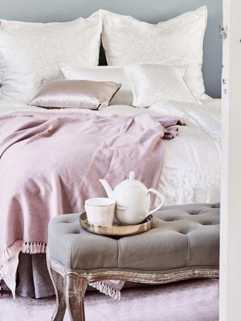 Habitación con manta rosa y banco pie de cama