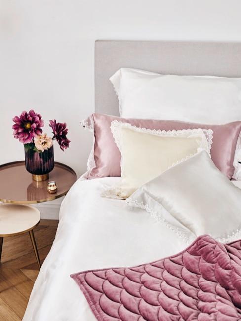 cama de color rosa con mesilla de noche y flores rosas